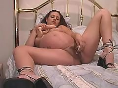Pregnant babe plays with huge dildo