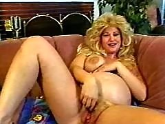 Pregnant blond girl relaxes on sofa